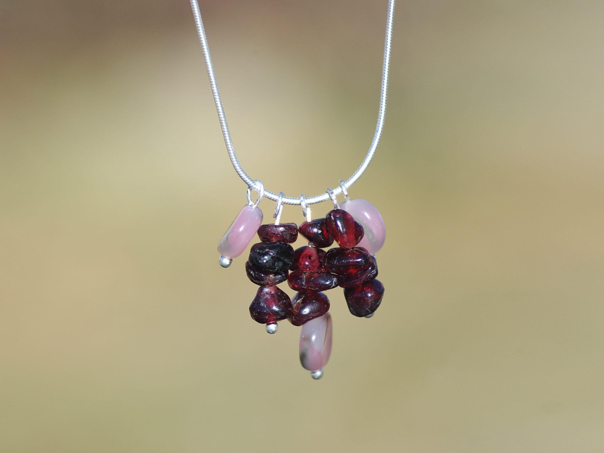 Fine chaîne serpentine avec un pendentif gemmes.Grenats presque bruts et des perles d'opales roses.