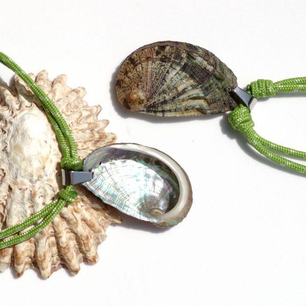 pendentif ormeau très brillant d'un côté, de couleur brun vert de l'autre côté, sur une cordelette marine verte. Noeuds coulissants