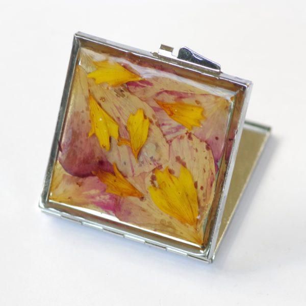 miroir de poche décoré d'un mélimélo de pétales roses et jaunes protégés par de la résine