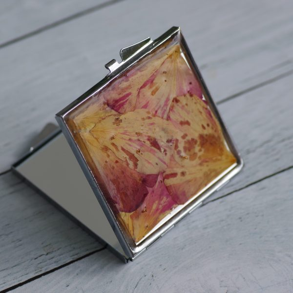 miroir de poche carré argenté très fin,avec un décor floral en inclusion : méli-mélo de pétales séchés (couleurs beige, rose, rouge)