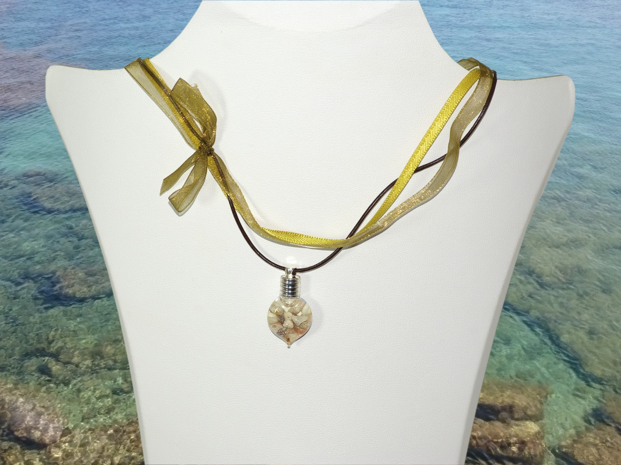 collier asymétrique vert, noué sur le côté en organza, satin et cuir, avec comme pendentif une fiole de verre remplie de coquillages.