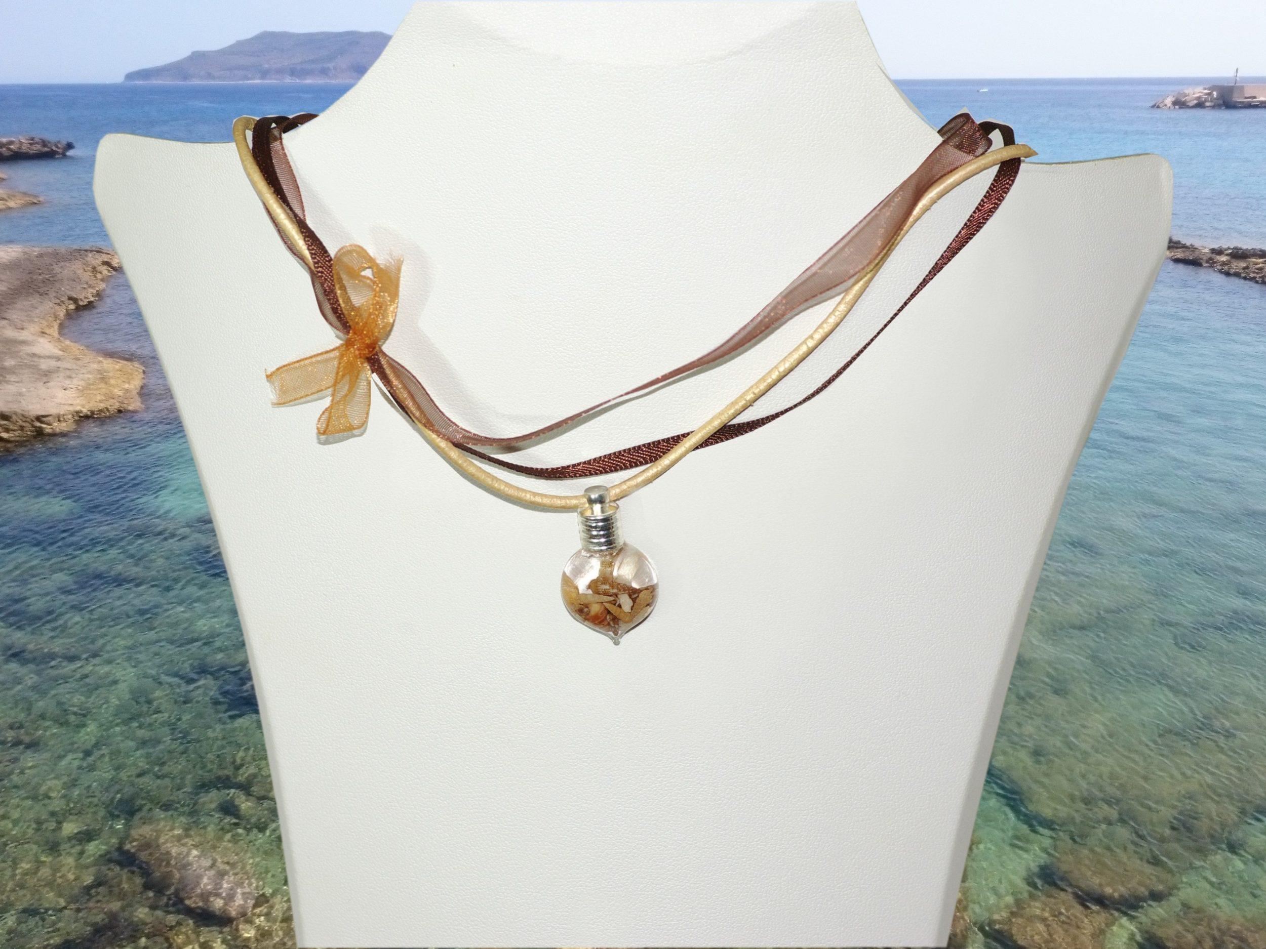 collier asymétrique aux couleurs naturelles, noué sur le côté en organza, satin et cuir, avec comme pendentif une fiole de verre remplie de coquillages.