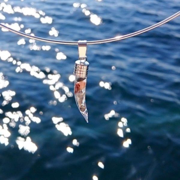 une fiole de verre en forme de corne renferme des mini coquillages, ce pendentf est monté sur un tour de cou rigide en inox