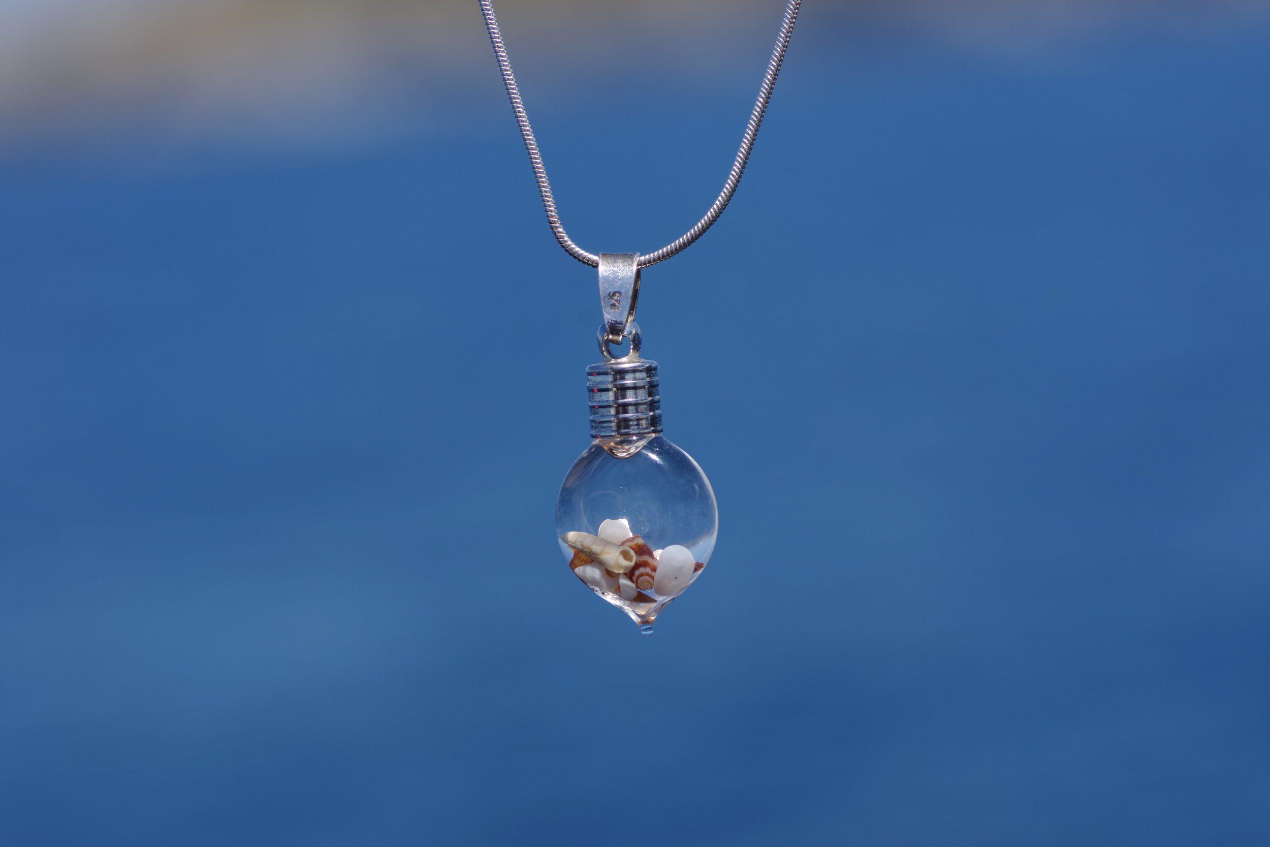 pendentif fiole de coquillages beiges sur une chaîne en argent fine style serpent. La fiole contient des coquillages blancs et beige et de l'eau