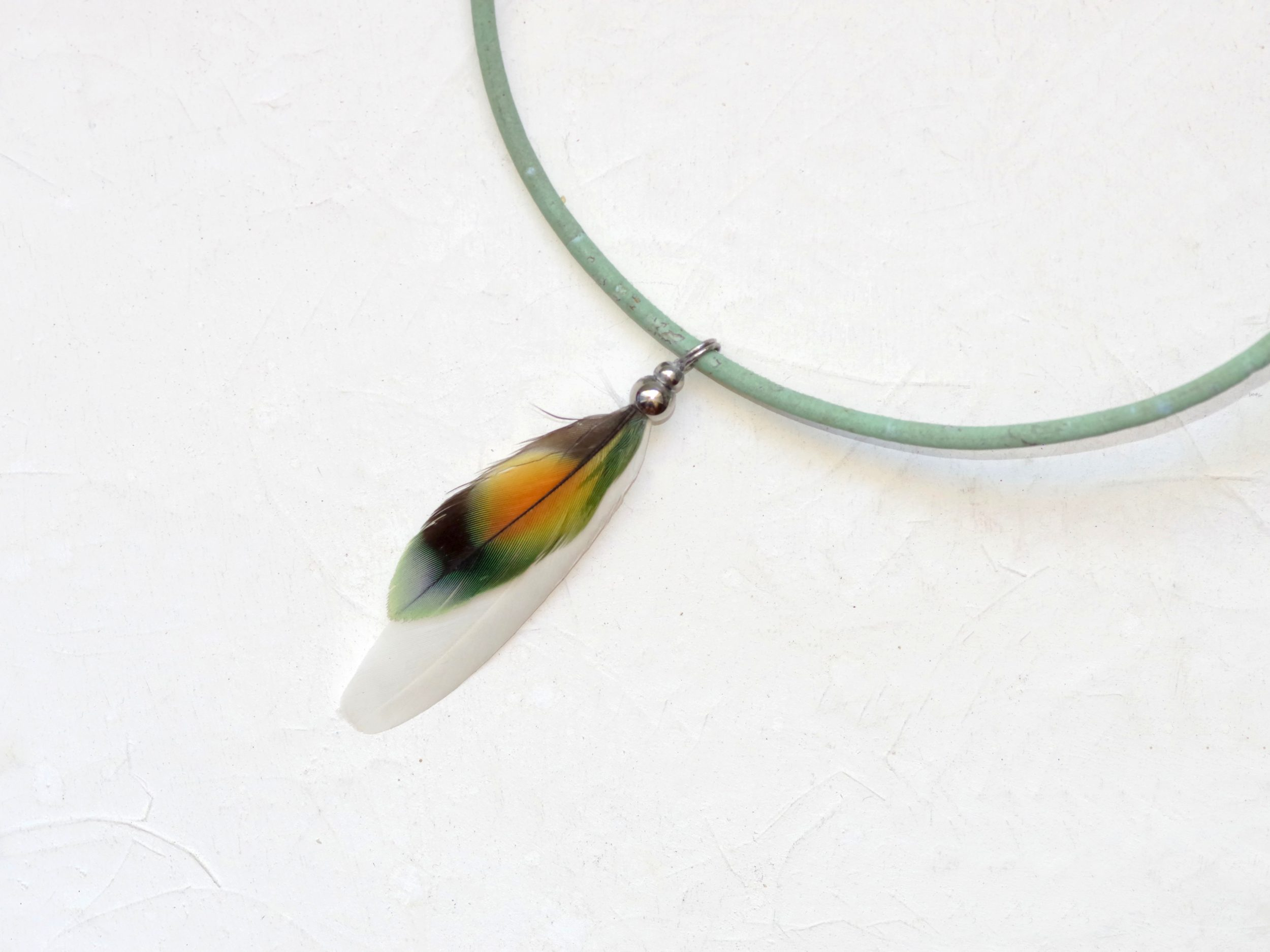 pendentif avec une plume de lovebird multicolore et une plume blanche, il est monté sur un cordon de liège vert d'eau (turquoise clair)