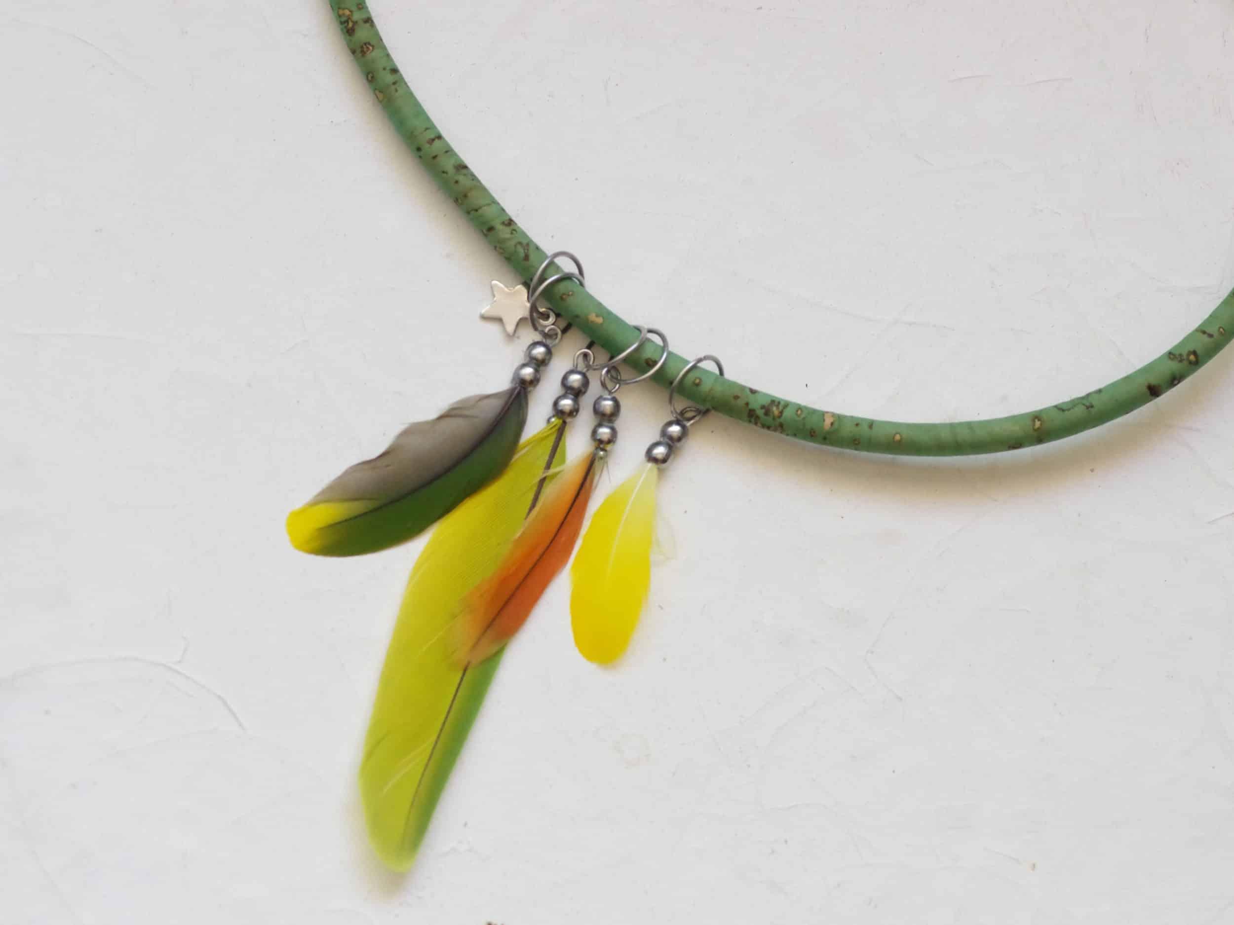 collier multicolore avec quatre pendentfs en plumes (jaune, verte, orange) et un petit pendentif étoile. Le tuur de cou est en liège vert
