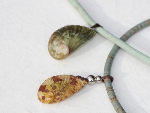 pendentifs réalisés avec des ormeaux de très belles couleurs : lun est vert-de-gris, l'autre brique et ocre jaune. Ils sont montés sur des cordons de liège teinté de jolies couleurs naturelles (vertd'eau, vert-de gris...
