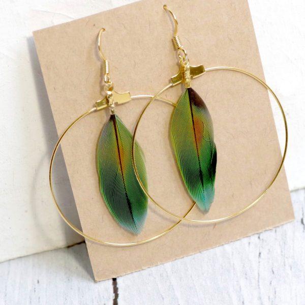 boucles d'oreilles avec des grands anneaux dorés et une plume verte et orange à l'intérieur. Joli dégradé de couleurs vert orange, bleu...