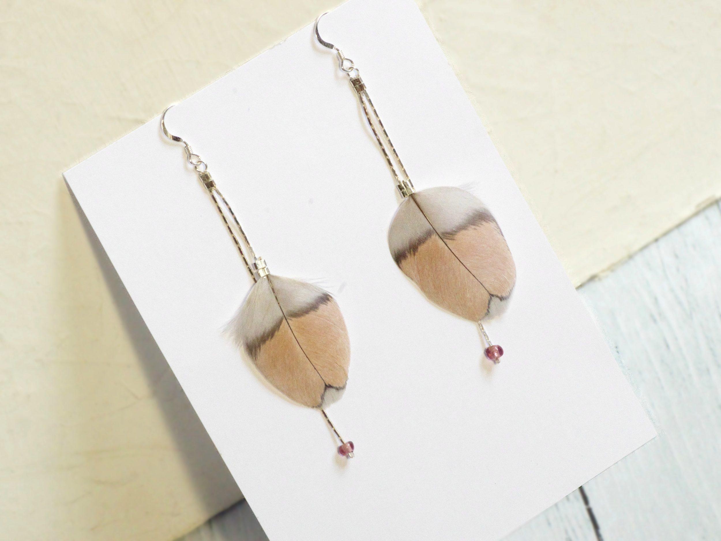 boucles d'oreilles avec des plumes originales aux couleurs douces gris et nude, et chaînes en argent, ponctuées par de petites perles en verre