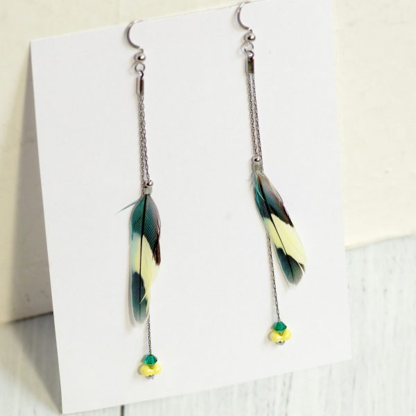 boucles d'oreilles à fines plumes bicolores : jaune pâle et bleu pétrole tirant sur le vert. Les plumes sont sur des chaînes très fines, une chaîne tient la plume l'autre est ponctuée de 2 petites perles assorties aux plumes.