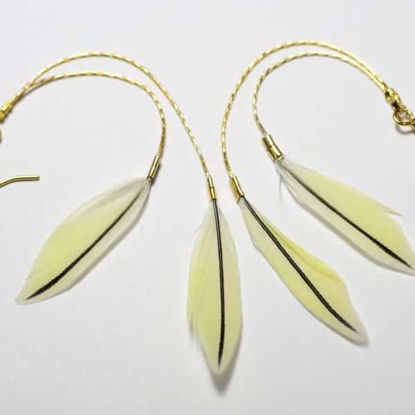 Boucles d'oreilles dorées : deux fines chaînes avec deux mini plumes jaunes pâles à ligne médiane noire