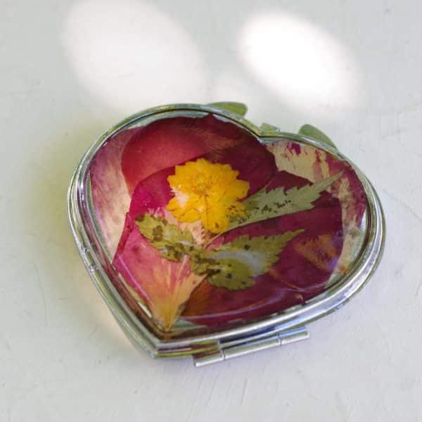 miroir coeur boitier métallique et décor floral : vraies fleurs et pétales rouges, roses, jaunes en inclusion dans de la résine. Il s'ouvre par clip .