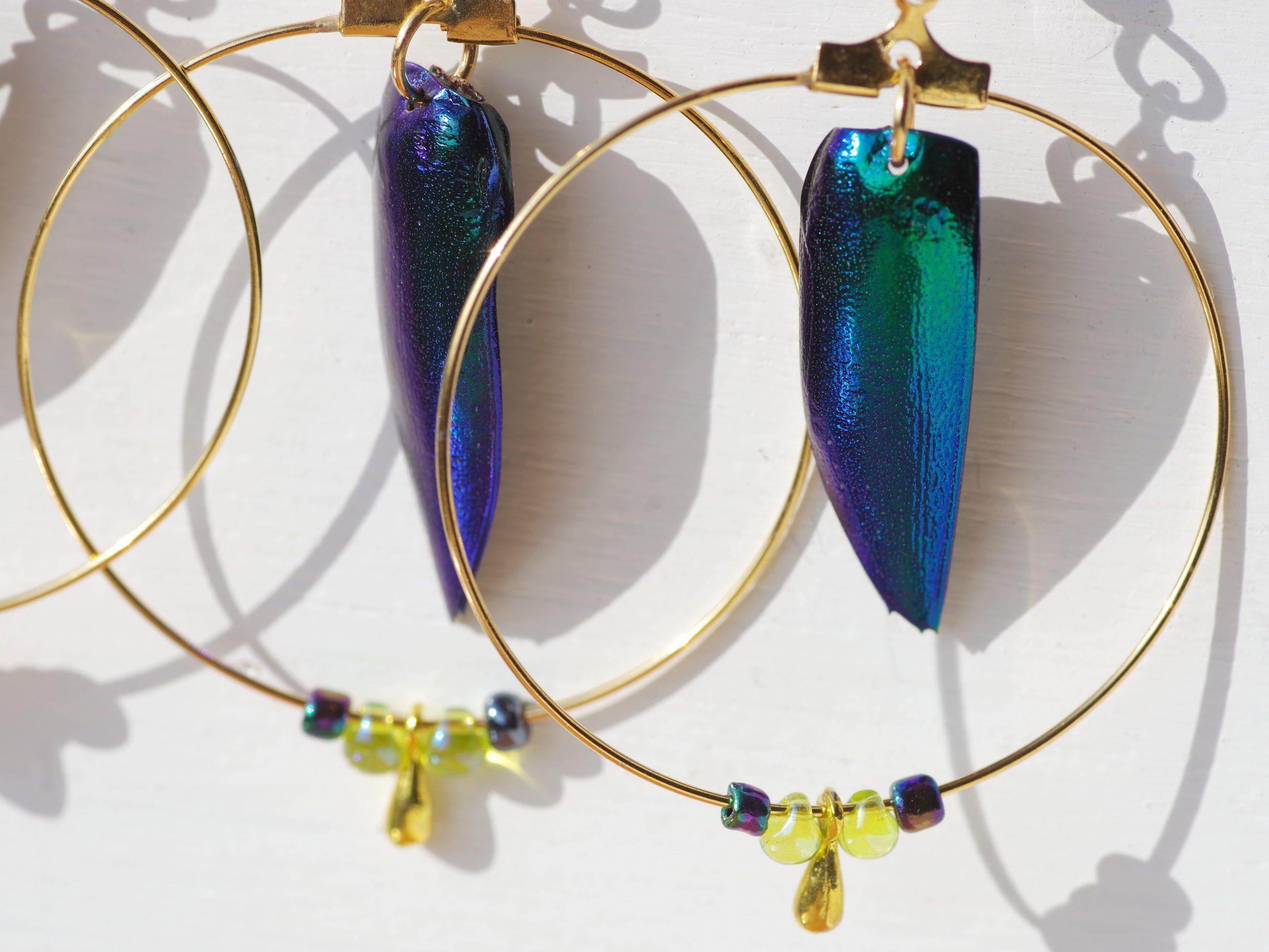 boucles d'oreilles dorées : grands anneaux dans les quels pendent des élytres bleu-vert de scarabée. Les couleurs sont chattoyantes avec des reflets métalliques. Petites perles de verre assorties.
