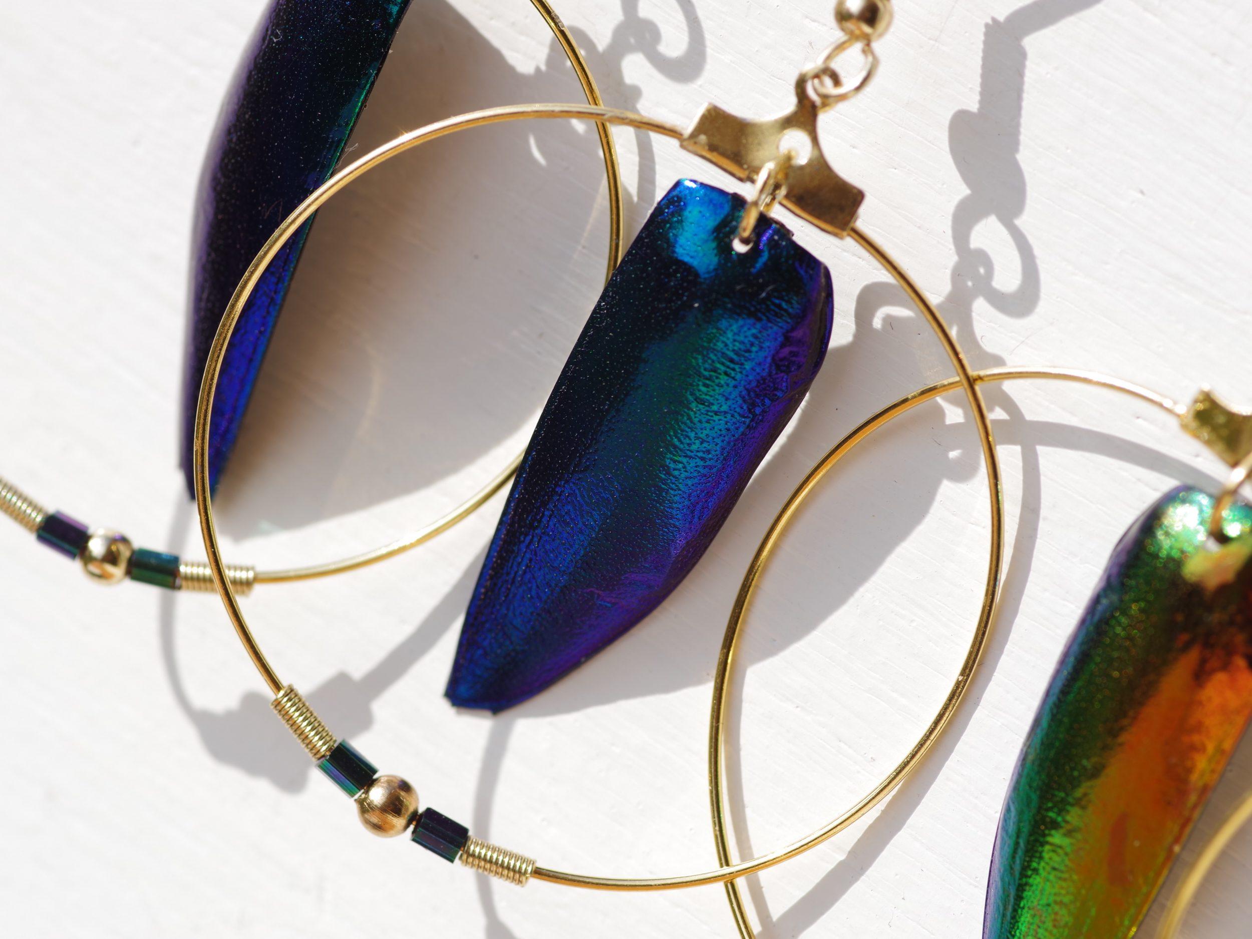 élytres bleus de scarabées aux reflets métallisés très brillants dans un anneau doré accompagnés de petites perles de verre bleu. ce sont des boucles d'oreilles minimalistes mais somptueuses