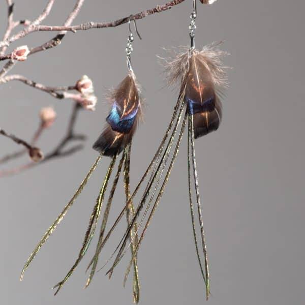 très fines et longues bouces d'oreilles plumes. Petites plumes brunes avec des reflets bleus et longues barbes de paon à reflets verts