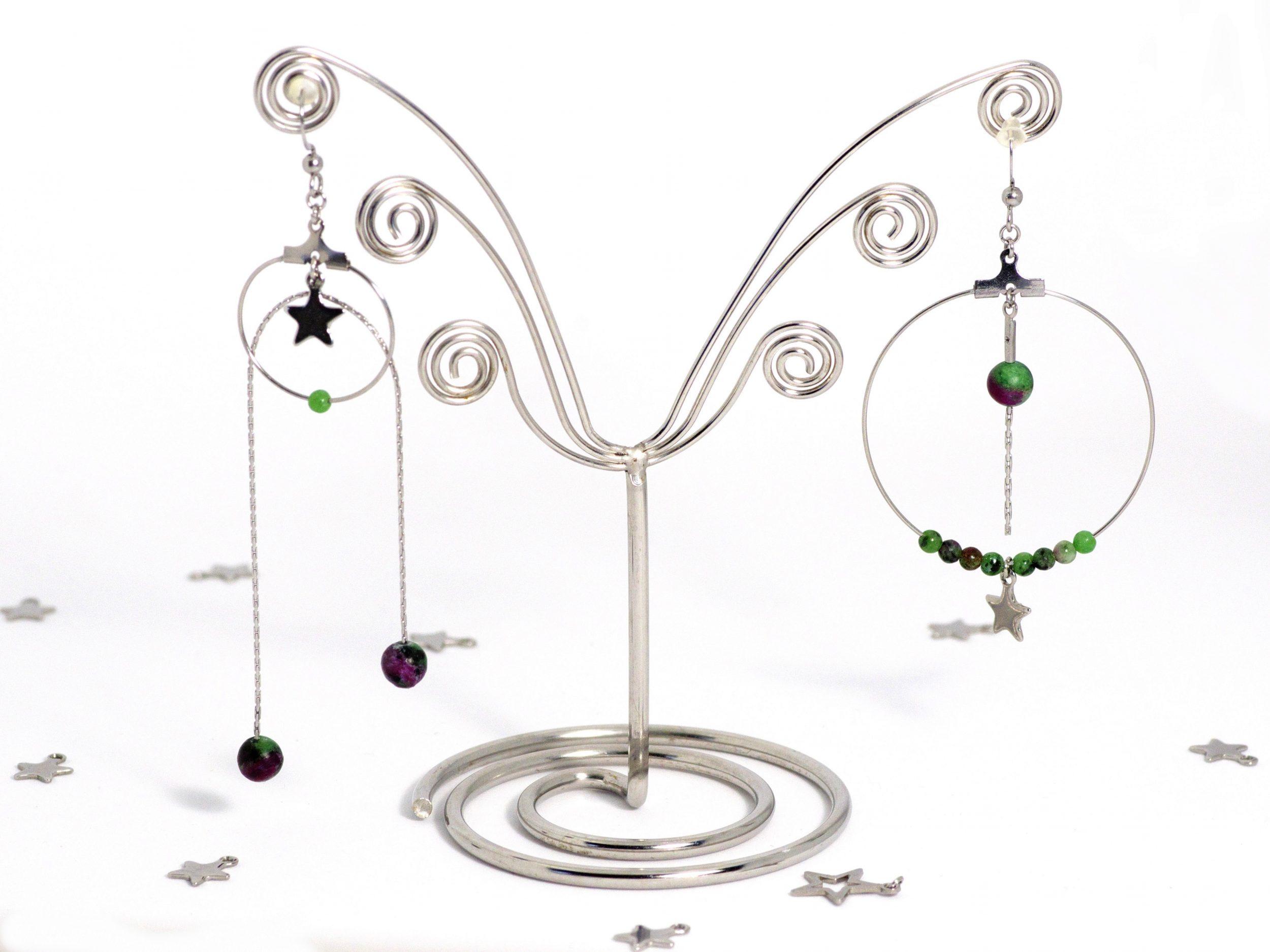 boucles d'oreilles asymétriques composées d'anneaux de différentes tailles , chaîne formant un arc de cercle et perles rondes vertes veinées de rouge, et petites étoiles argentées.
