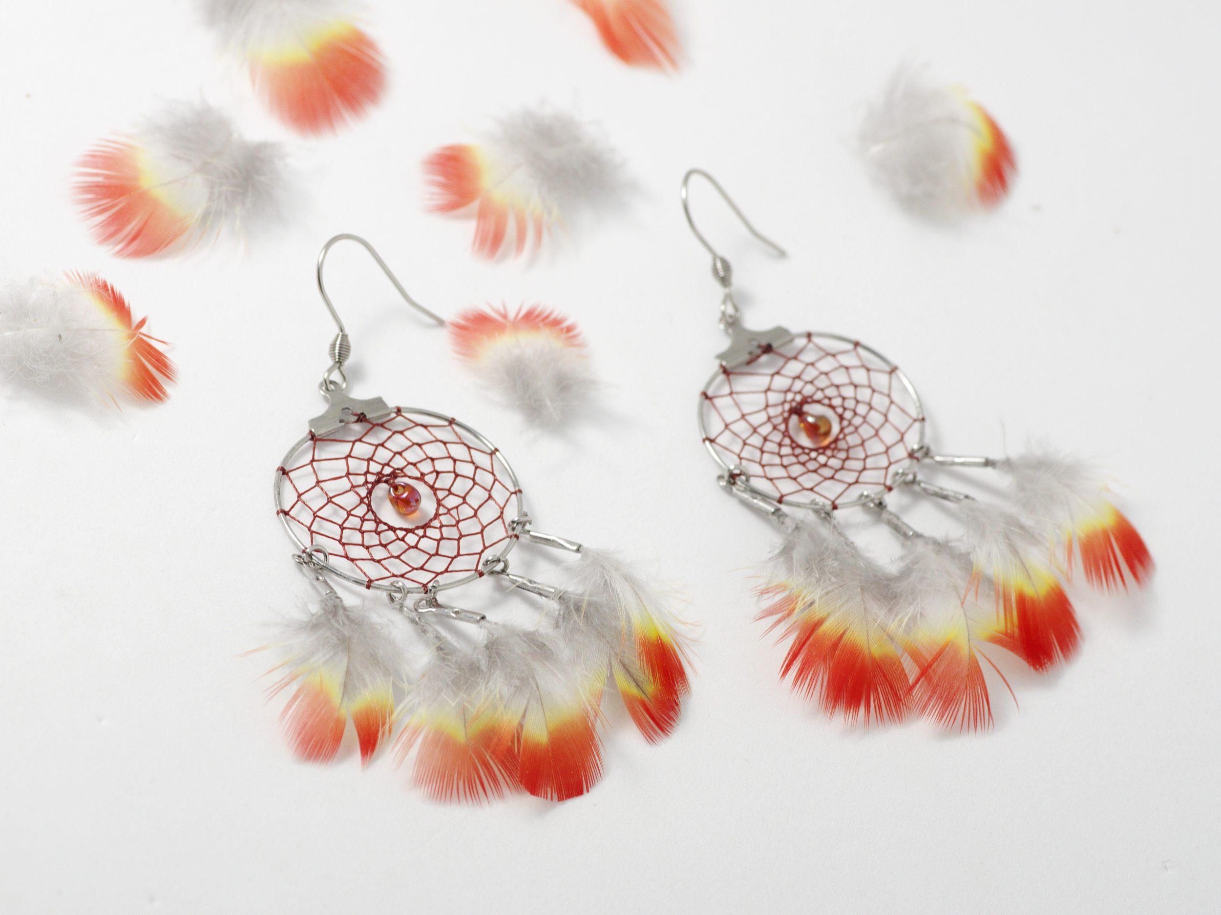boucles d'oreilles dreamcatchers avec de mini plumes rouges et jaunes et une toile finement tissée rouge sombre sur un anneauen inox