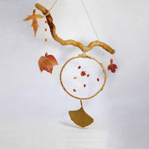 dreamcatcher végétal destructuré : le capteur de rêves et des feuilles d'automne sont acrrochés à un bois flotté tortueux, la composition est asymétrique. au coeur il y a une baie de fusain avec des graines orange vif