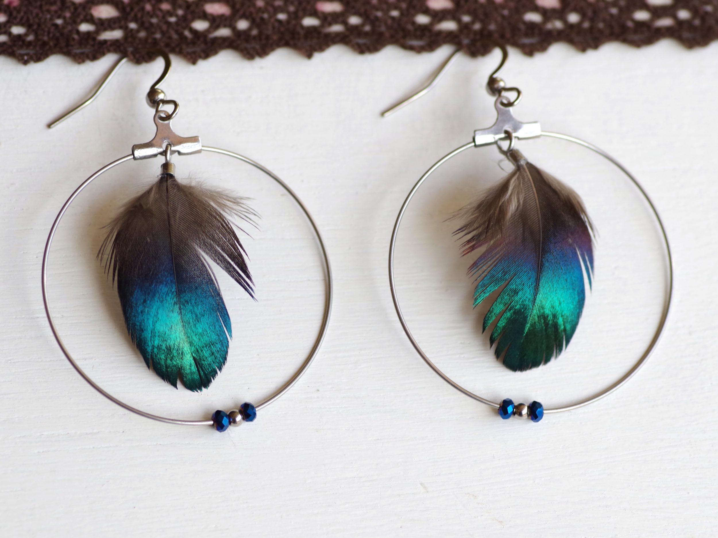 boucles d'oreilles à plumes bleues aux reflets brillants dans des anneaux argentés agrémentés de trois petites perles assorties aux plumes