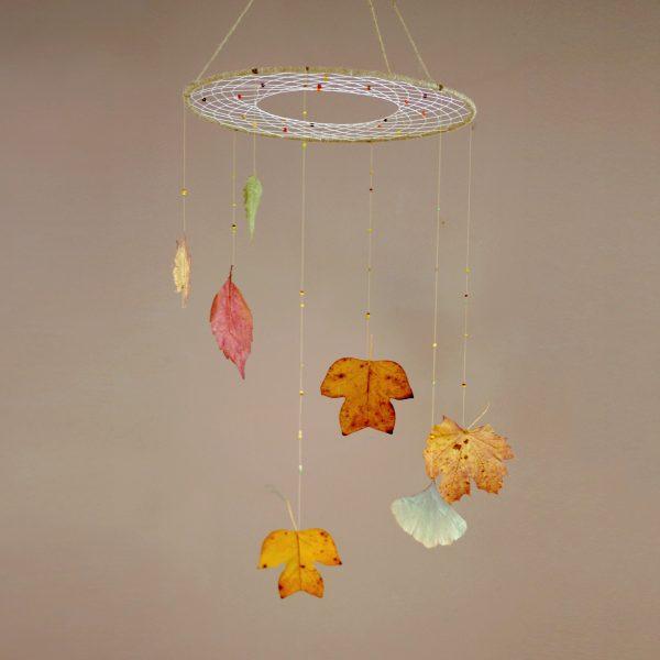 capteur de rêves végétal composé d'une toile de dreamcatcher horizontale avec une spirale de feuilles supendue en dessous, tons naturels