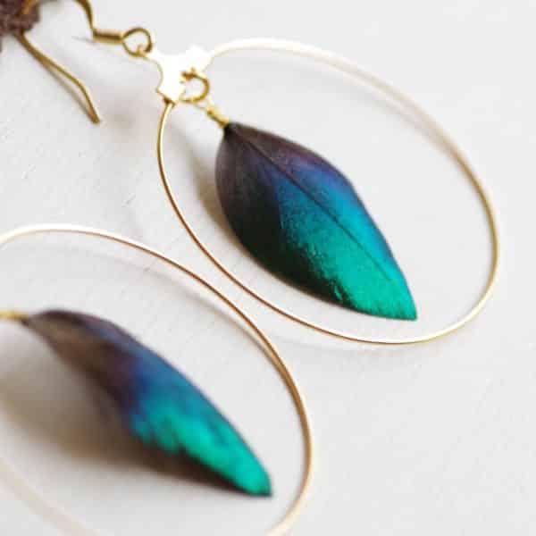 boucles d'oreilles créoles dorées avec à l'intérieur des plumes bleu turquoise très brillantes