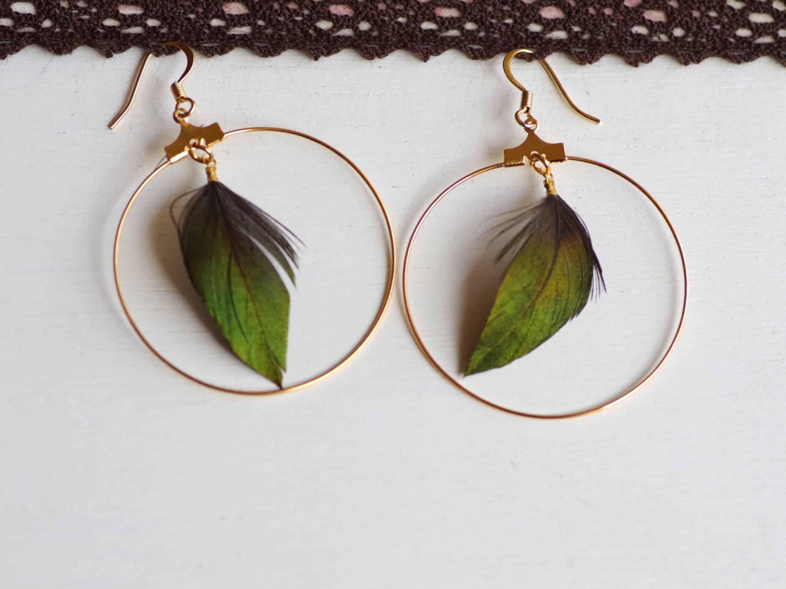 boucles d'oreilles créoles dorées avec une plume verte brillante triangulaire dans l'anneau