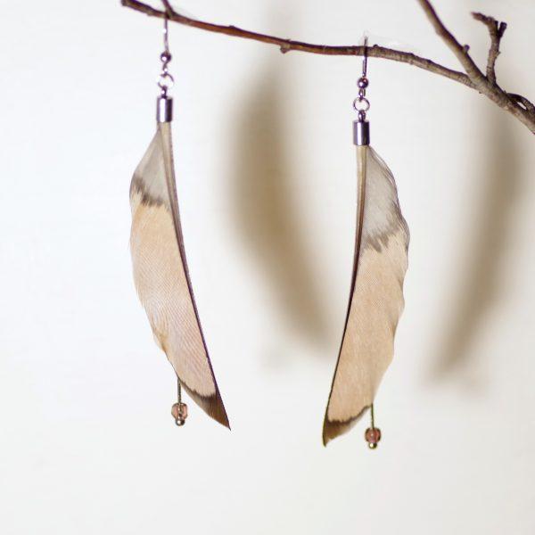 Longues et fines boucles d'oreilles plumes, très élégantes et originales. Les plumes sont coupées le long de l'axe pour obtenir un fin croissant de lune. Elles sont mises en valeur par de fines chaînes en inox et de toutes petites perles en verre. Les couleurs sont douces : gris et nude, soulignées par du brun foncé sur la pointe.