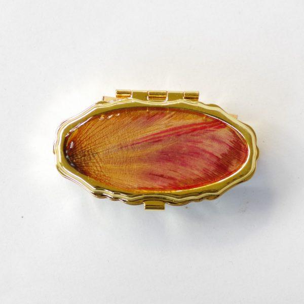 petite boite à pilumes ovale , boitier métallique doré et décor végétal rouge orangé. à l'intérieur : 2 compartiments