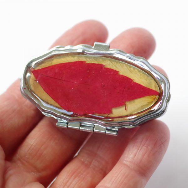 petite boite ovale avec sourire : décorée d'une vraie feuille rouge ressemblant à une bouche qui sourit