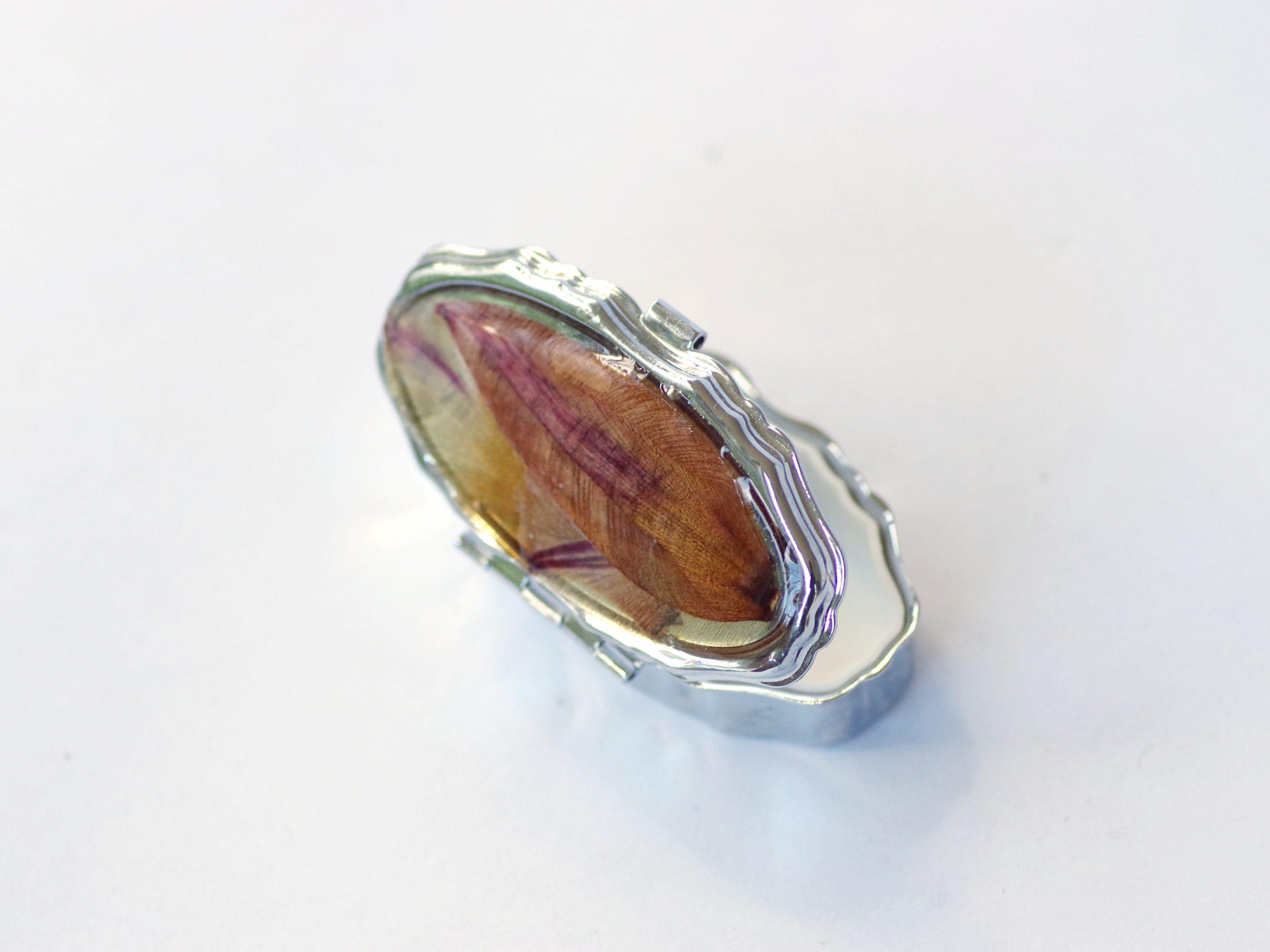 petite boite à pilules ovale décorée de pétales dans des tons orangés, boitier métallique argenté