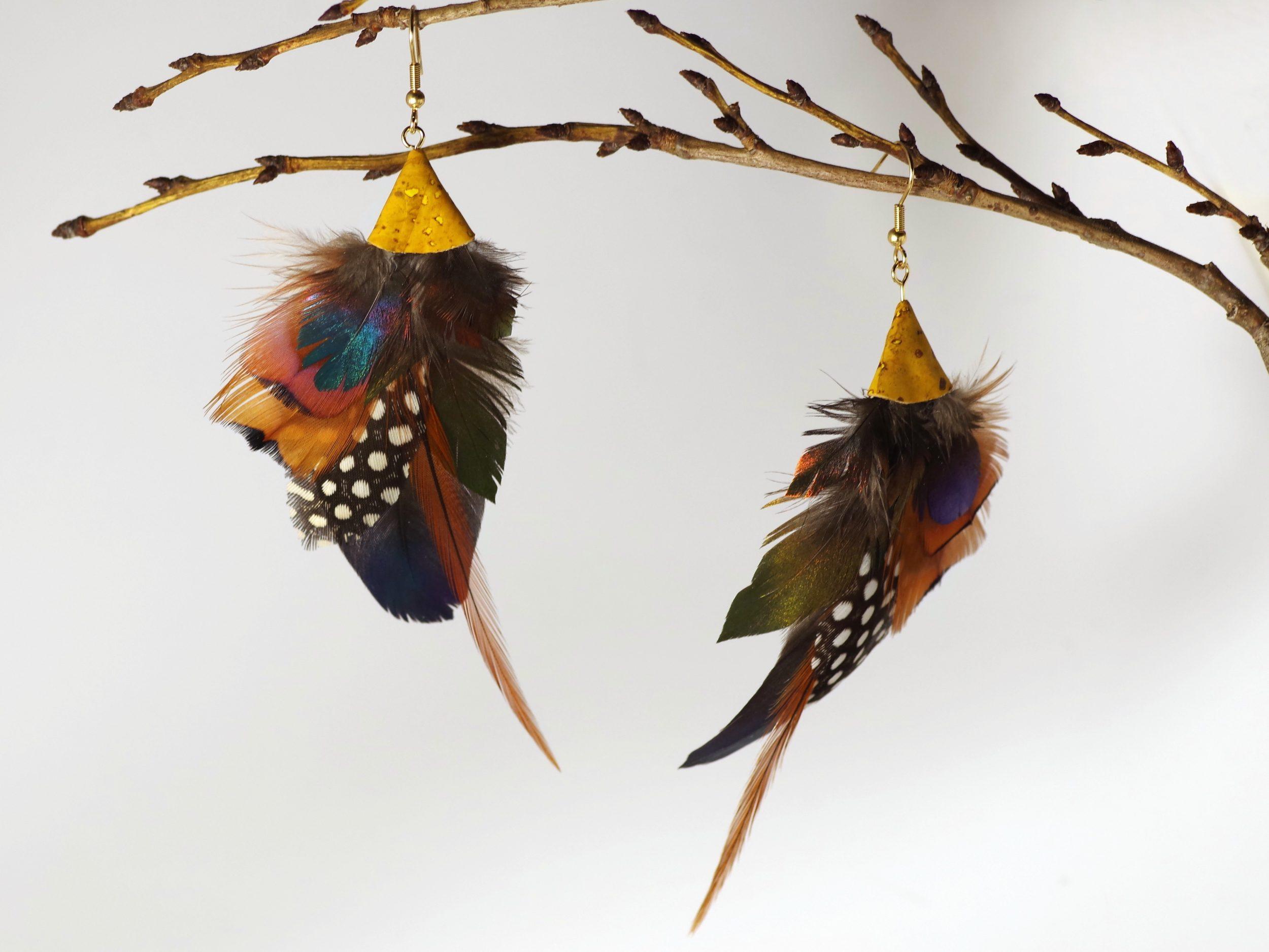 grandes bouces d'oreilles en plumes multicolores naturelles, couleurs vives et reflets marron, cuivré, bleu foncé, reflets turquoise, vert, pois noir et blanc