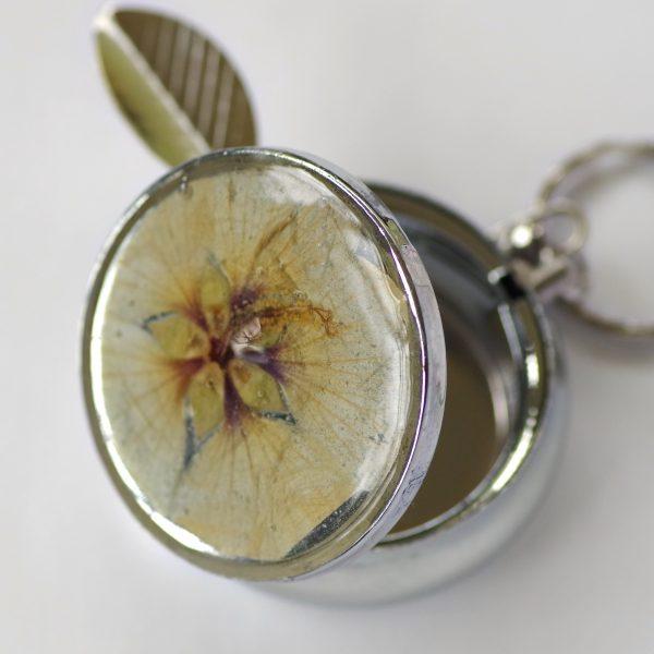 cendrier de poche décoré d'une vraie fleur blanche en inclusion dans de a résine. Boitier argenté avec repose cigarette et anneau d'accrochage