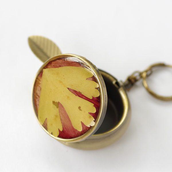 cedrier de poche couleur bronze, décor végétal rouge et jaune. Petit repose cigarette et anneau d'accrochage