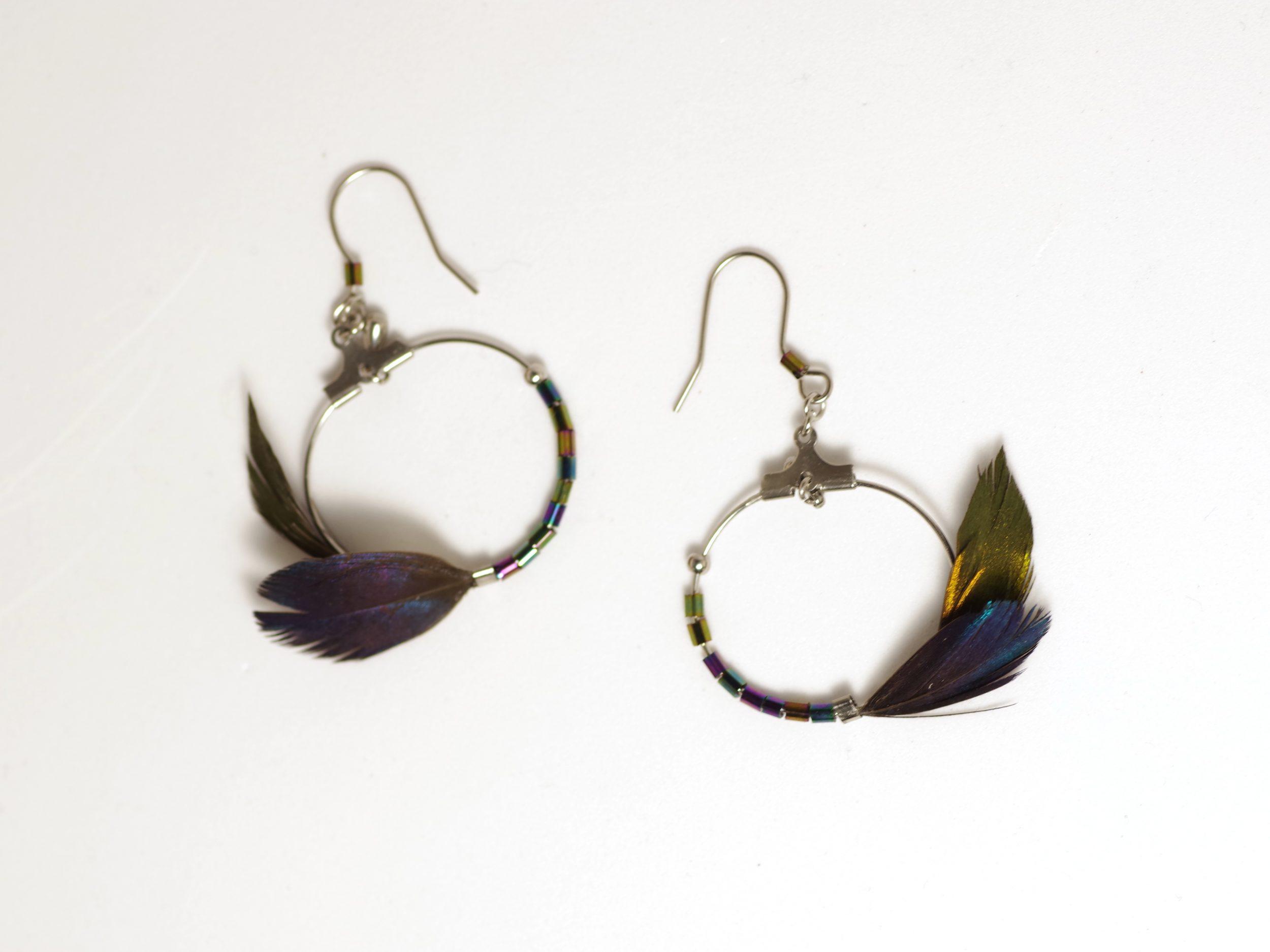 boucles d'oreilles avec un petit anneau inox décoré de façon asymétrique avec deux petites plumes à reflets brillants et des perles assorties