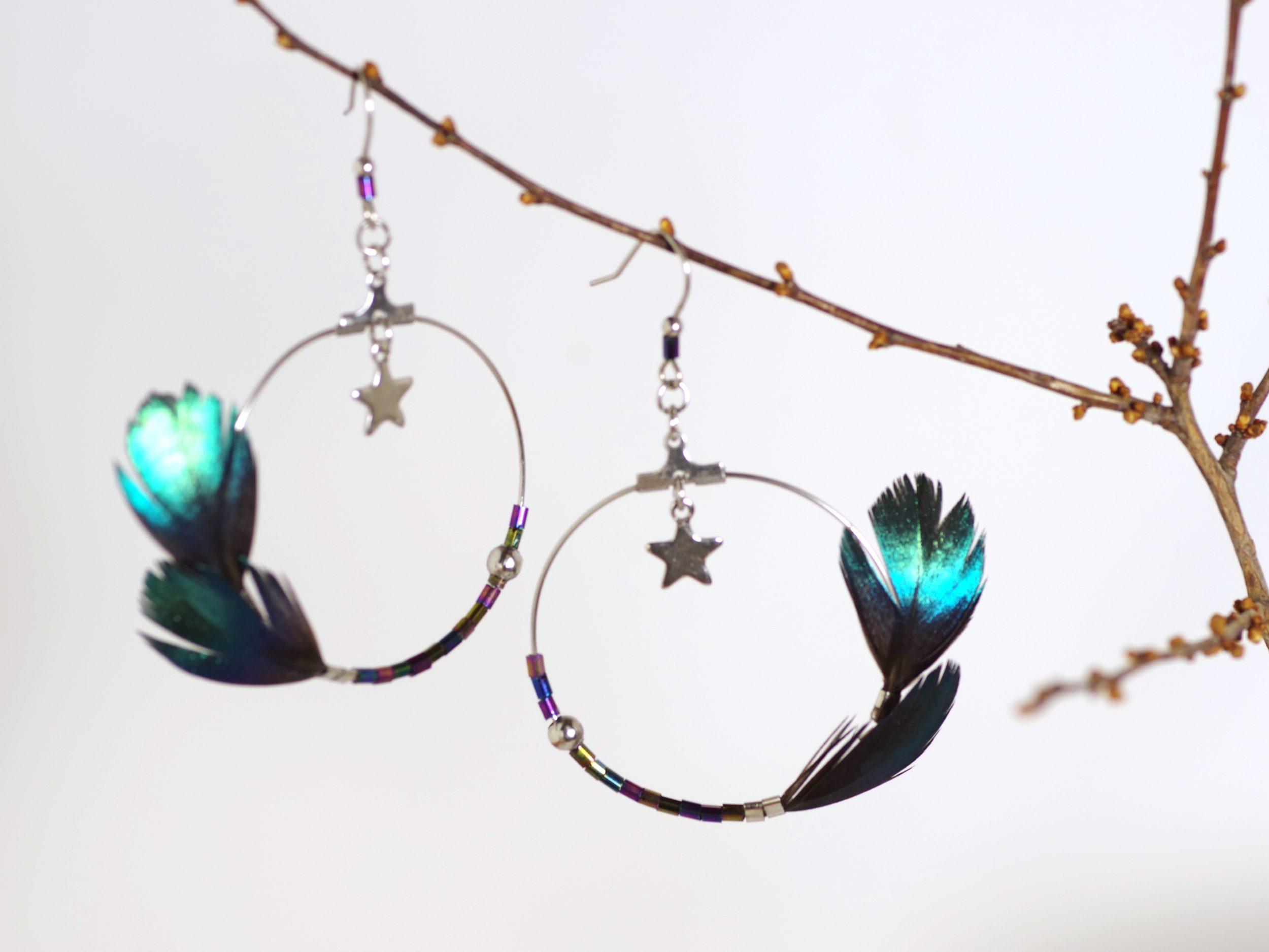 boucles d'oreilles avec de grands anneaux asymétriques décorés d'un côté avec des plumes bleu-vert brillantes et de l'autre avec de petites perles aux couleurs assorties aux plumes