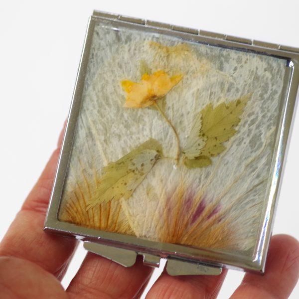 miroir de poche à décor floral : une petite fleur jaune sur un fond de pétales pâles, boîtier argenté