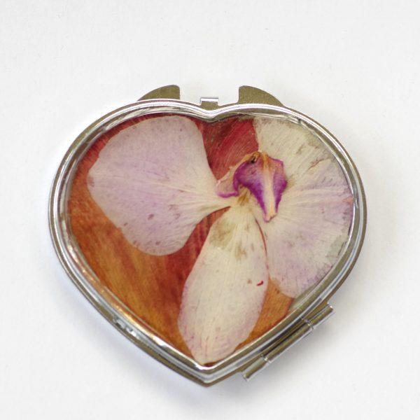 miroir de poche en forme de coeur décoré d'une orchidée parme sur fond rouge orangé, boitier métal argenté