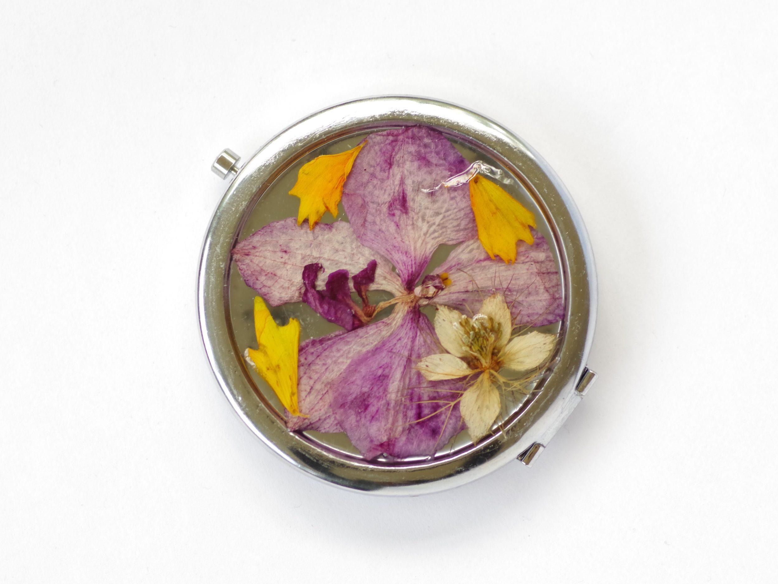 miroir de poche rond avec une décorfloral : orchidée violette et petites fleurs champêtres. Boitier en métal argenté ouverture poussoir