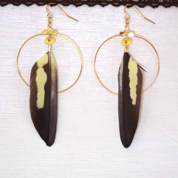 boucles d'oreilles composées d'unegrande plume de canari supperosée à un grand anneau doré et accompagnée de petites pelres jaunes assorties aux plumes. Les plumes sont gris-brun avec une longue tache jaune pâle