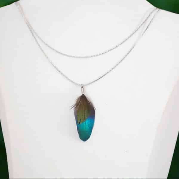 collier composé de deux fines chaînes argentées et un pendentif avec deux plumes brillantes : une bleue et une petite verte