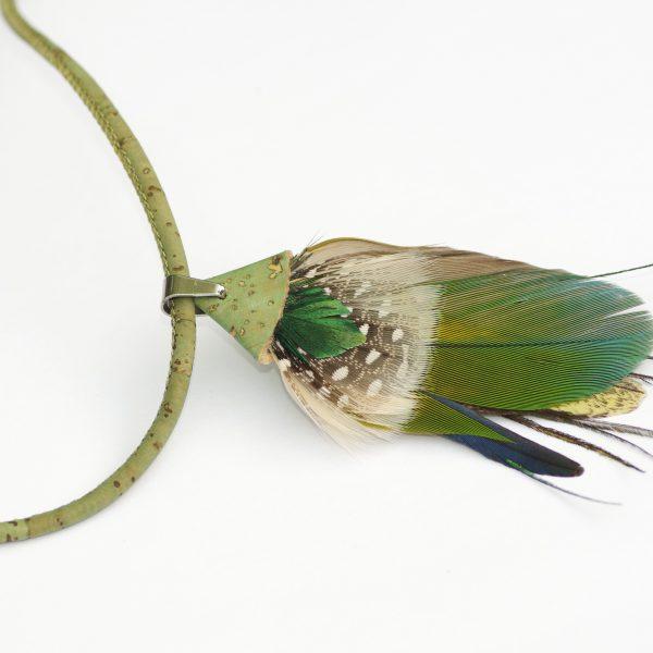 collier en liège avec en pendentif une composition de plumes bleu-vert maintenue par un triangle de liège vert. Il ya une grande plume vert-bleu, une blanc cassé, une grise à pois bancs, une fine jaune et une fine bleue.