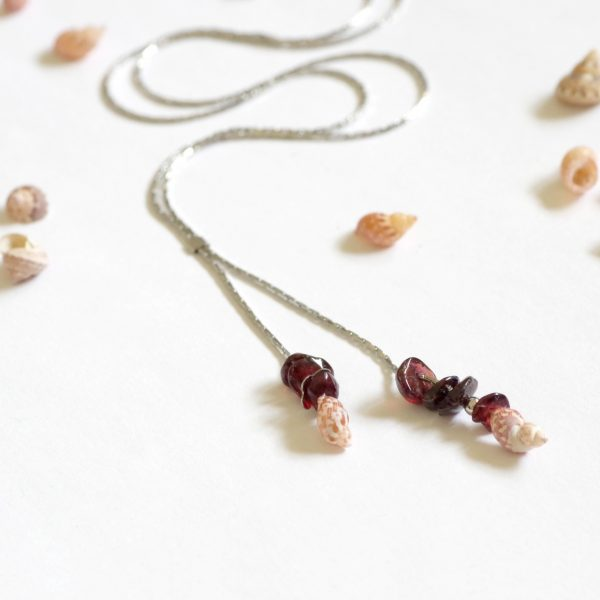 collier minimaliste : chaîne très fine en inox , les deux bouts de la chaîne forment deux pendentifs, avec quelques pierres de grenats et un mini coquillage