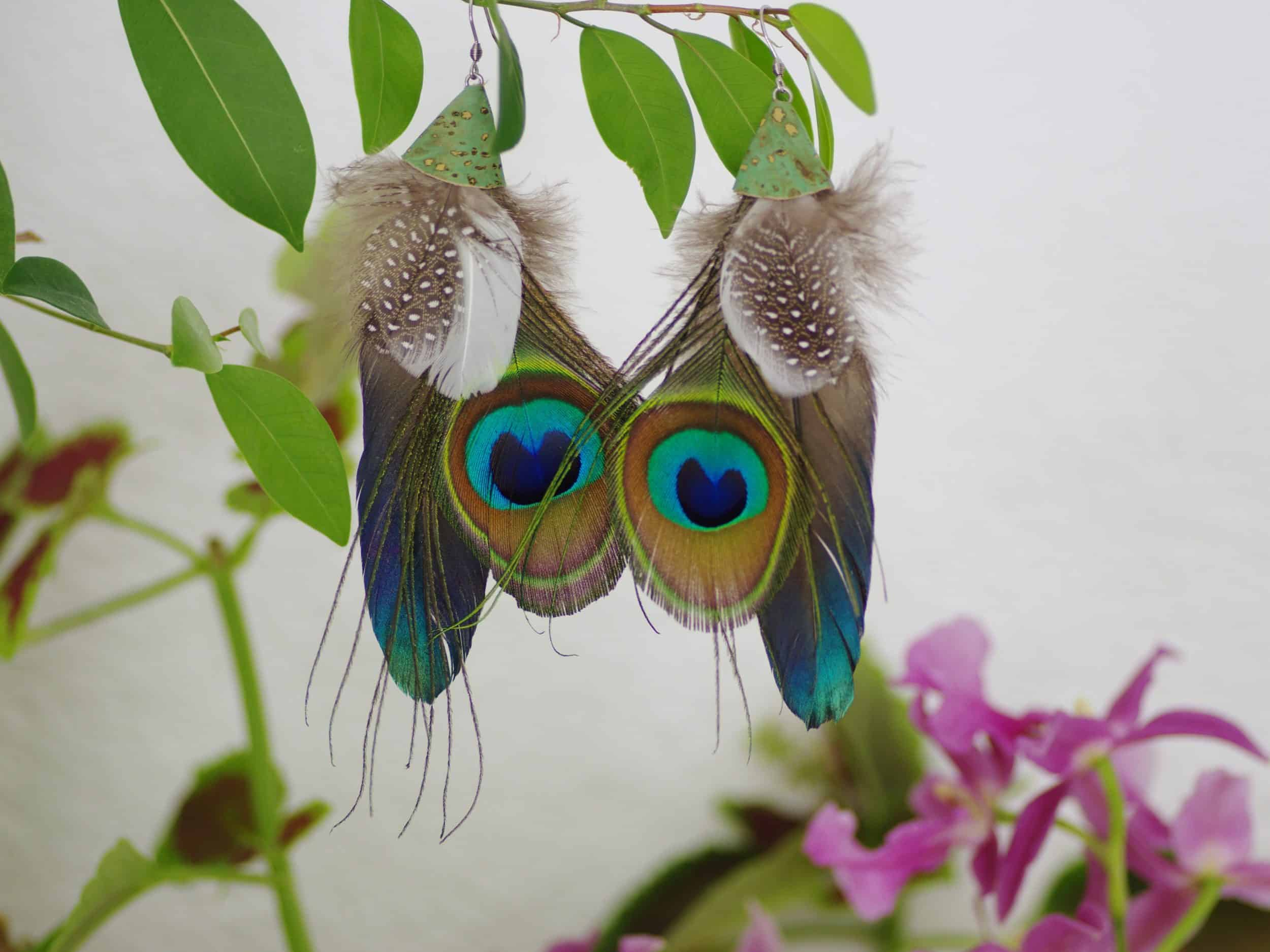 grandes boucles d'oreilles au style ethnique: composition avec oeil de paon associé à une grande plume bleue et des plumes blac et gris à pois blancs