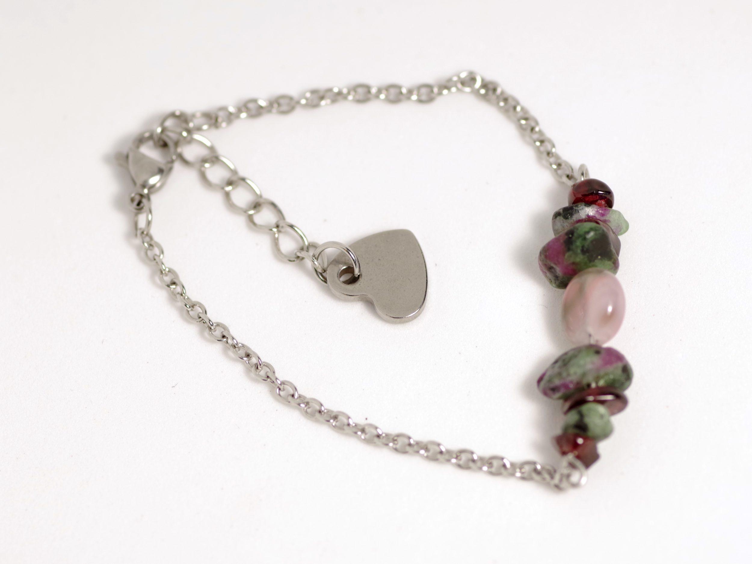 bracelet avec une chaîne en inox, quelques pierres rouges, roses, vertes et un coeur en inox au bout du fermoir réglable