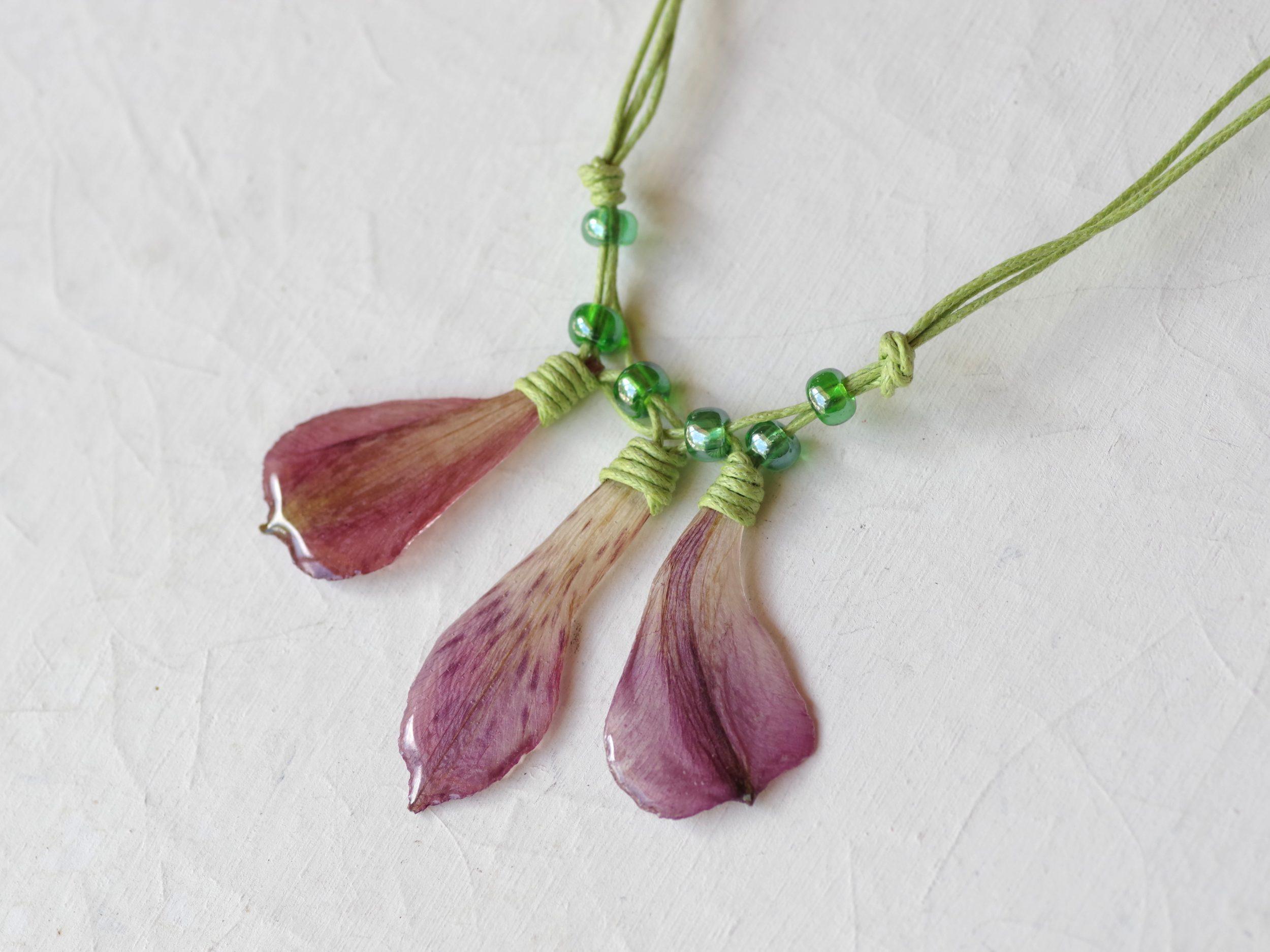 collier vert et violet composé de plusieurs pétales violets en pendentis et liens de coton vert acidulé noués et entrelacés. alstromérias