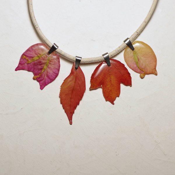 collier réalisé avc des feuilles rousses et des fleurs de bougainvillier sur un cordon de liège blanc cassé.