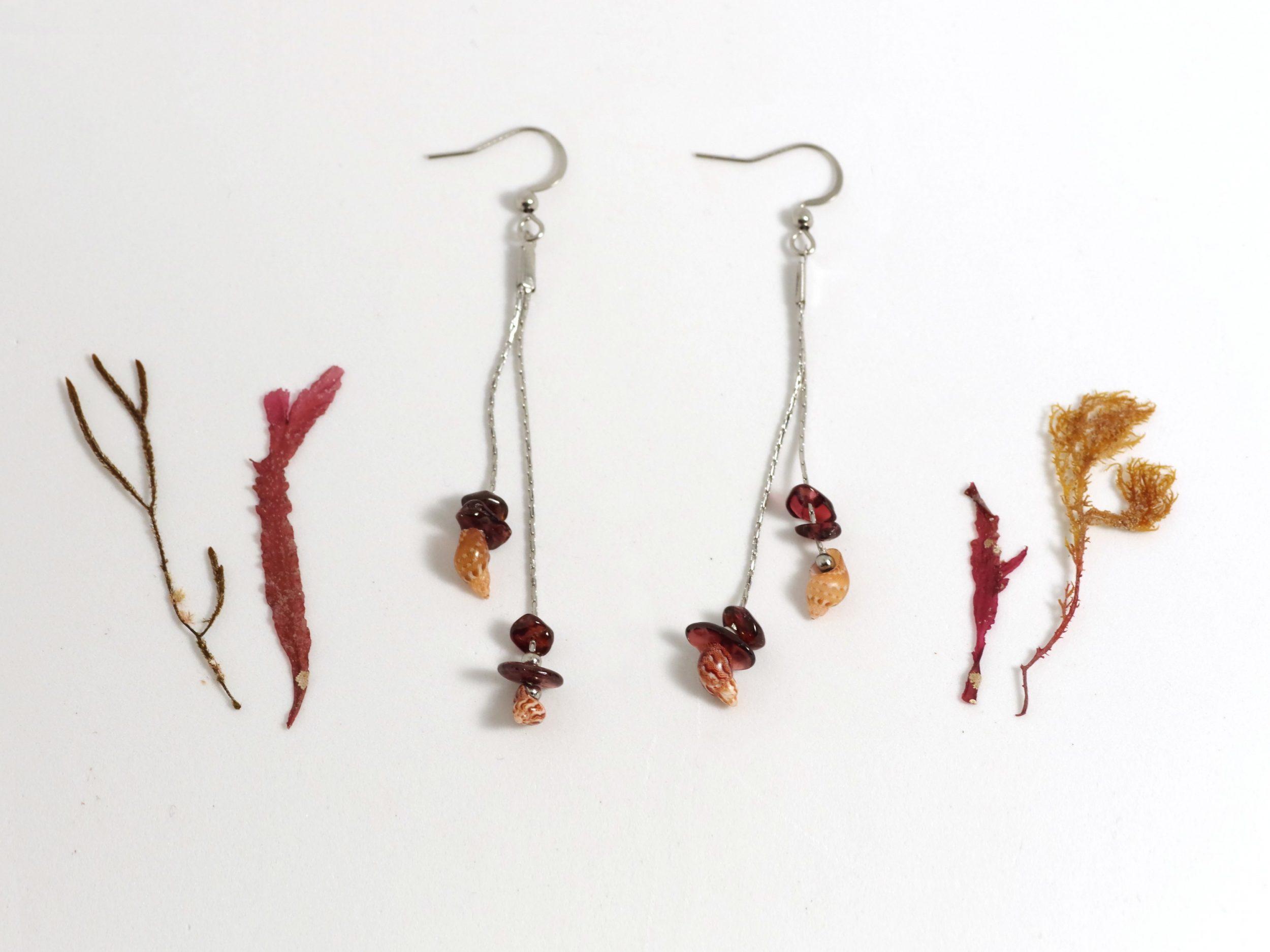 boucles d'oreilles longues avec deux fines chaînes en inox, au bout de chaque chaîne un petit coquillage associé à quelques grenats