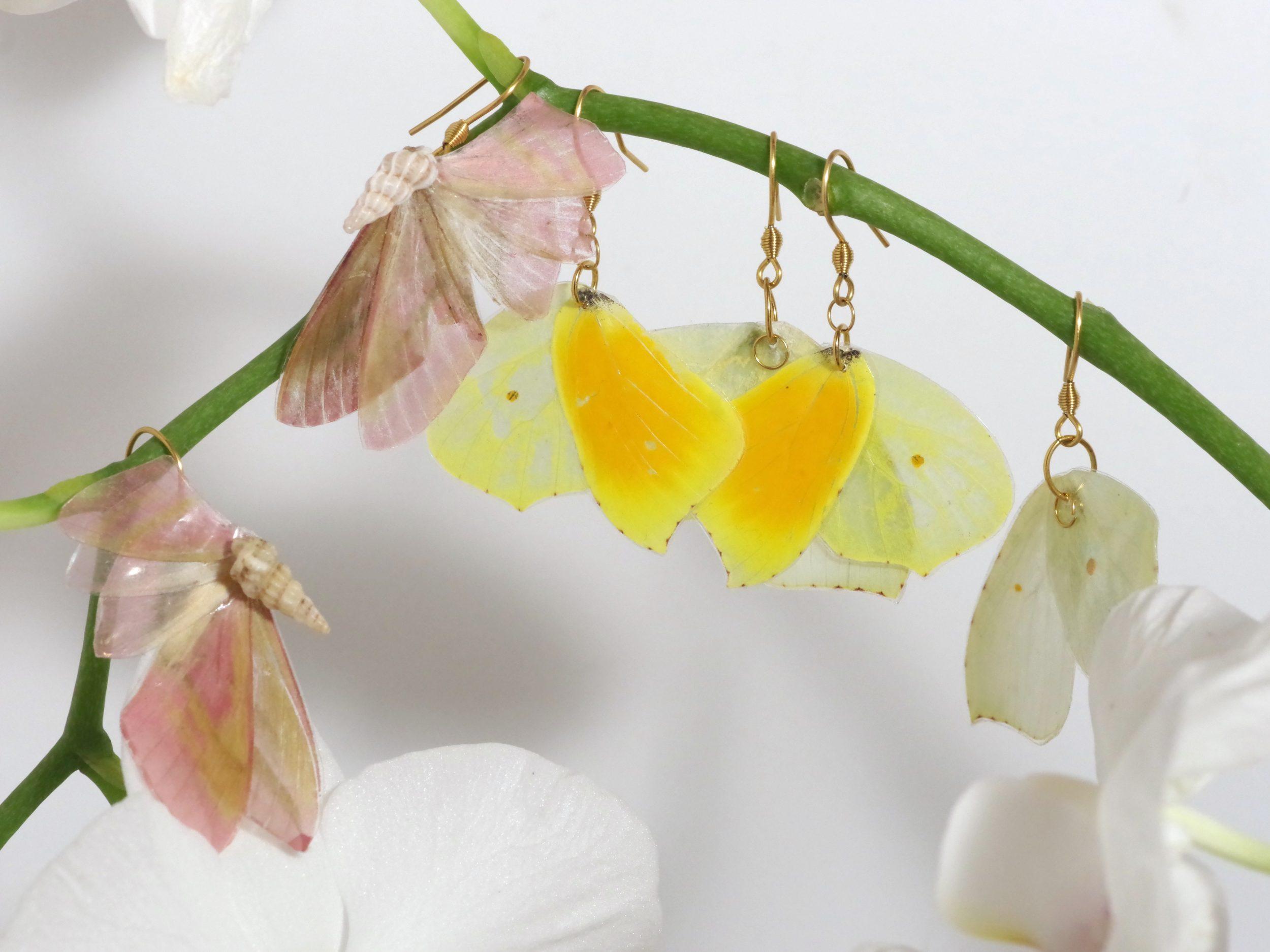 """plusieurs paires de boucles d'oreilles réalisées avec des ailes de papillon. Chaque bijou est un """"demi-papillon"""". Couleurs rose, jaune pâle, orange vif."""