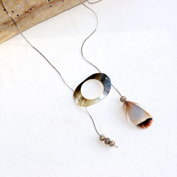 long collier sautoir en inoxen forme de H avec un double pendentif dont une plume. Les deux pendentif sont reliés par un rond de nacre.
