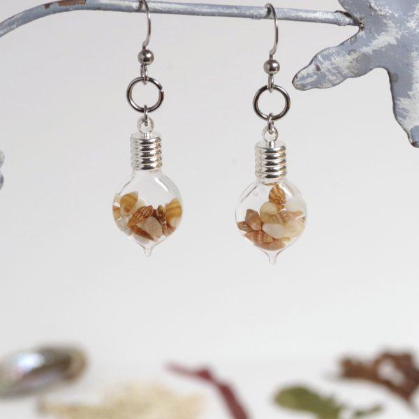 boucles d'oreilles originales , de petites fioles de verres remplies de macrocoquillages beiges, gris et bruns
